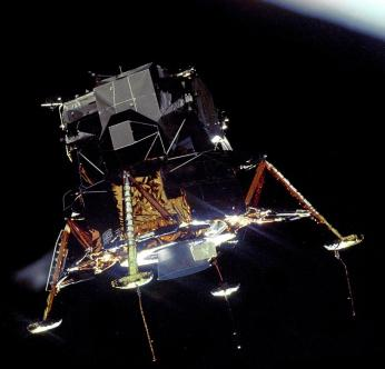 """Apollo 11 Lunar Module Eagle in Landing Configuration in Lunar Orbit from the Command and Service Module Columbia."" 1969. https://en.wikipedia.org/wiki/File:Apollo_11_Lunar_Module_Eagle_in_landing_configuration_in_lunar_orbit_from_the_Command_and_Service_Module_Columbia.jpg."