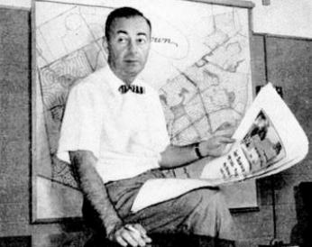 William Levitt posing with a map of his suburb