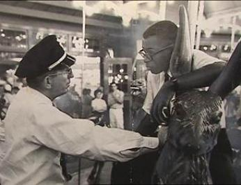 Officer Frank Collins confronts Laurence Henry on Glen Echo's Dentzel Carousel on June 30, 1960. (Photo source: National Park Service)