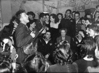 Pete Seeger performing at a party at the Congress of Industrial Organizations canteen in Washington DC in 1944, as First Lady Eleanor Roosevelt looks on. Credit: Library of Congress.