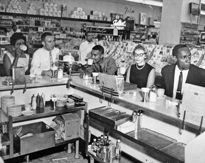 Non-violent Action Group members enjoy a cup of coffee at an Arlington Drug Fair lunch counter on June 23, 1960, one day after the counter was integrated. (Source: Washington Area Spark on Flickr.)