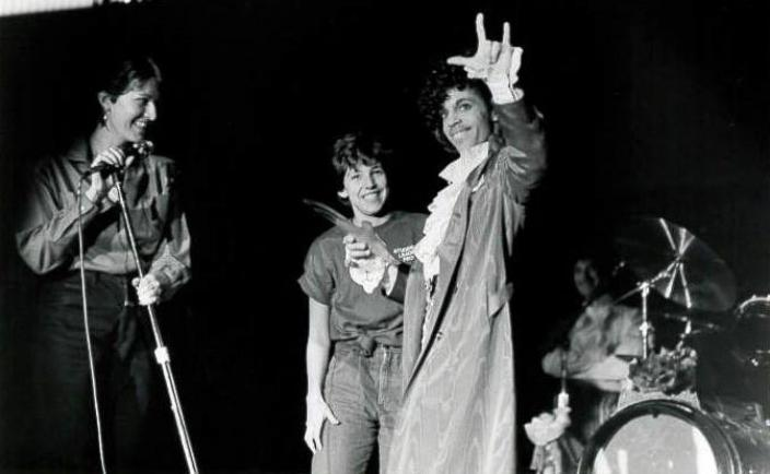 "Prince returns the ""I Love You"" sign while being presented with a gift by student representatives. (Photo: Courtesy of the Gallaudet University Archives)"