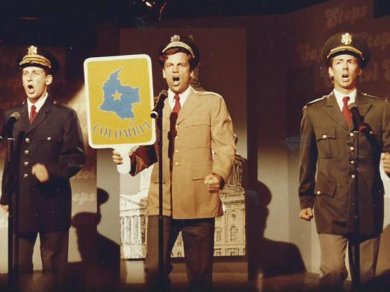 """Three men performing on stage at WETA with a sign that says """"Columbia""""."""