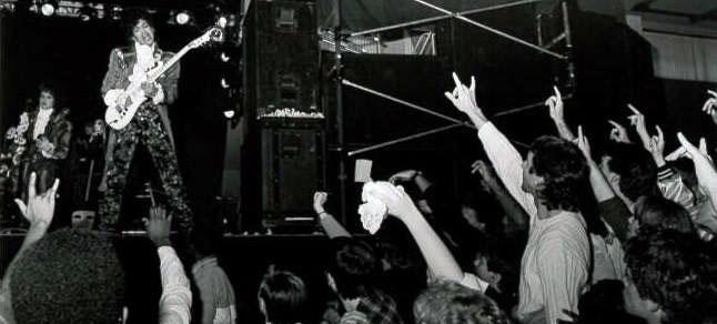 """Prince on stage mid-performance, with the crowd throwing up """"I Love You"""" signs. (Photo: Courtesy of the Gallaudet University Archives)"""