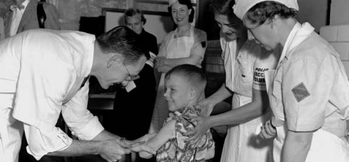 Dr. Richard Mulvaney administers the trial Polio vaccine to Randall Kerr with two nurses looking on