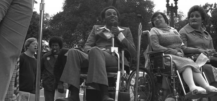 Brad Lomax, center, next to the activist Judy Heumann at a rally in 1977 at Lafayette Square in Washington. (Photo by HolLynn D'Lil)