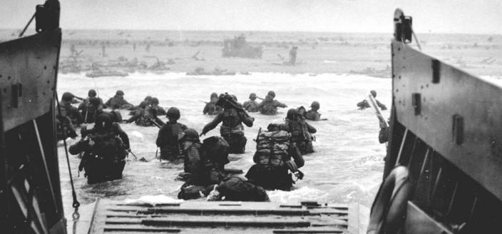 U.S. Soldiers disembark a landing craft at Normandy, France, June 6, 1944. By the end of the day some 150,000 Allied troops had landed on five Normandy beaches and three airborne drop zones. The invasion marked the beginning of the final phase of World War II in Europe, which ended with the surrender of Germany the following May. (Source: Wikimedia Commons, U.S. Department of Defense photo courtesy of the National Infantry Museum/Released)