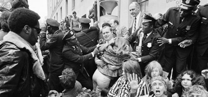 An employee of the Justice Department is helped over demonstrators blocking the entrance to the building in Washington, May 1, 1971