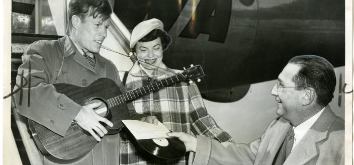 """From left to right, Jimmie Dodd and his wife, Ruth, are presented with a record of """"Washington"""" by James H. Simon."""