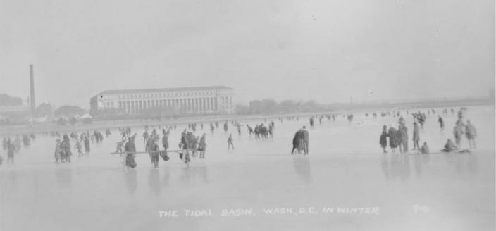 Black and white photo of people ice skating and walking on the Tidal Basin