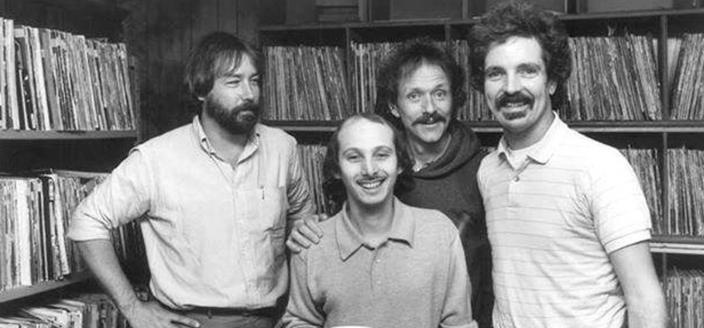 WHFS deejays Damian Einstein (far right) and Weasel (front) pose with musician Jesse Colin Young (second from right) and an unidentfied record executive (far left) at WHFS headquarters in Annapolis, MD in 1983.  (Photo source: Handout photo/Steve King).