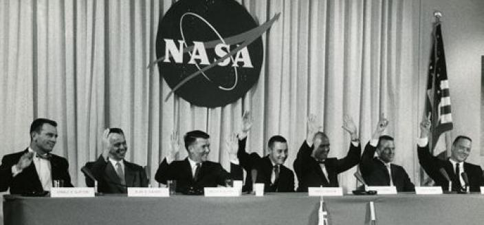 """The Mercury 7 astronauts (left to right) Slayton, Shepard, Schirra, Grissom, Glenn, Cooper, and Carpenter all raise their hands in reply to a question about whether they felt confident they would return from space – Glenn raised both hands,"" 1959 (Photo Source: NASA) https://www.nasa.gov/feature/60-years-ago-nasa-introduces-mercury-7-astronauts"