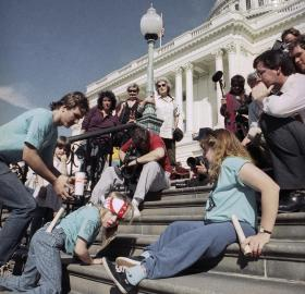 Jennifer Keelan-Chaffins wears a bandana as she crawls up the U.S. Capitol steps on her hands and knees. On her left is a man bending over and on her right a woman moves up the stairs on her back. All three protesters wear matching light blue shirts from the ADAPT organization. In front of them are media personnel with cameras and microphones recording the protest. [Photo Credit: Associated Press]