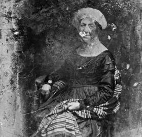 Dolley Madison in 1848, seated at a table