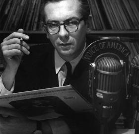 A young and serious Willis Conover, cigarette in one hand, jazz record in the other, in his Voice of America studio. Source: Wikimedia Commons
